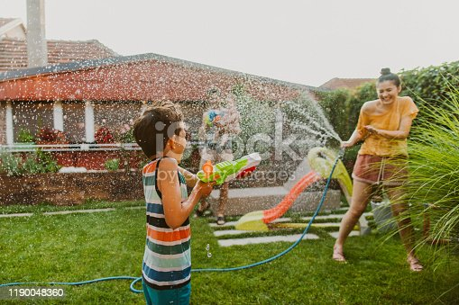 Photo of family water fight in the yard