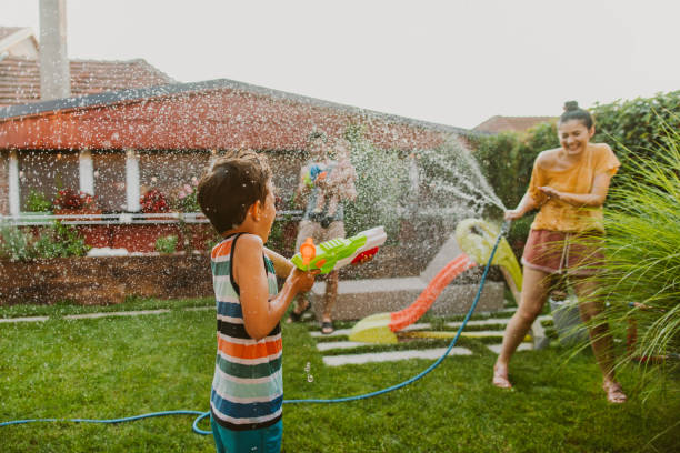 Family water fight in the yard stock photo