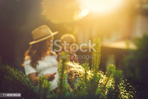 Happy child and his mother watering plants  in spring or summer day