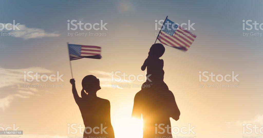 Family waving American flags Patriotic silhouette of family waving American USA flags. 20-29 Years Stock Photo