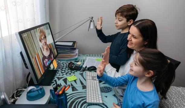 Familie winkt auf Videoanruf mit Großmutter – Foto