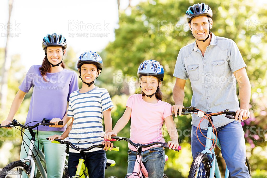 Family Wearing Helmets While Holding Bicycles In Park stock photo