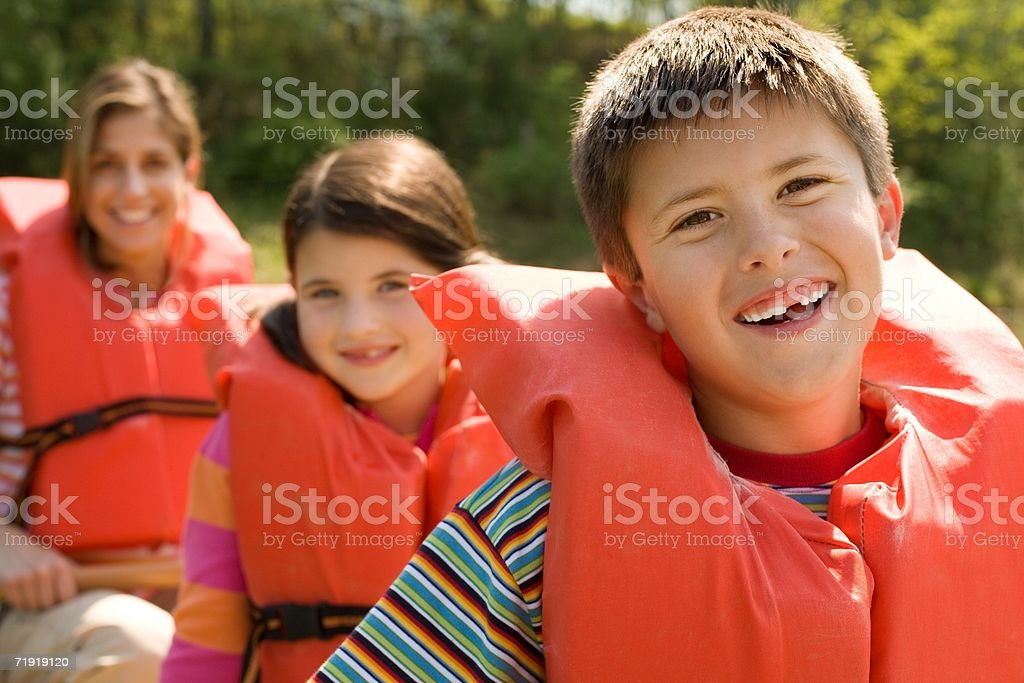 Family wearing life jacket in boat royalty-free stock photo