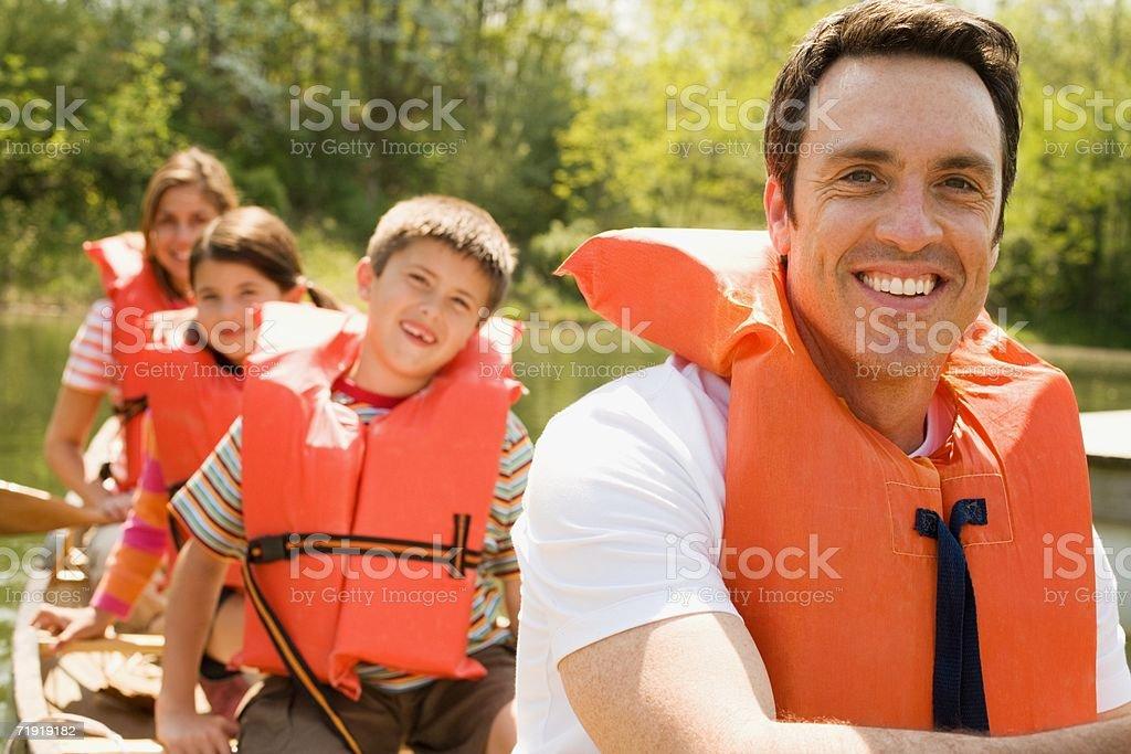 Family wearing life jacket in canoe royalty-free stock photo