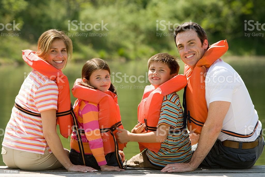 Family wearing life jacket sitting on jetty royalty-free stock photo