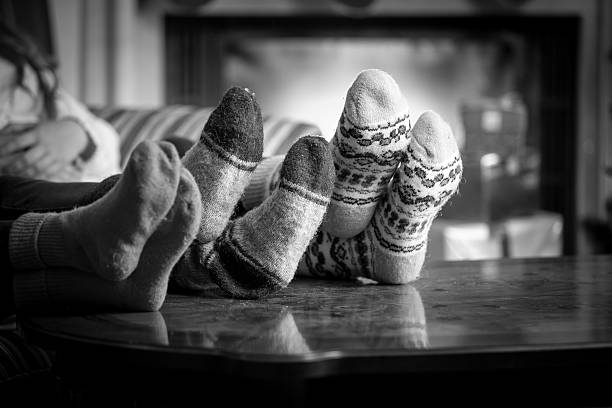 family wearing woolen socks warming at fireplace Closeup black and white photo family wearing woolen socks warming at fireplace desaturated stock pictures, royalty-free photos & images