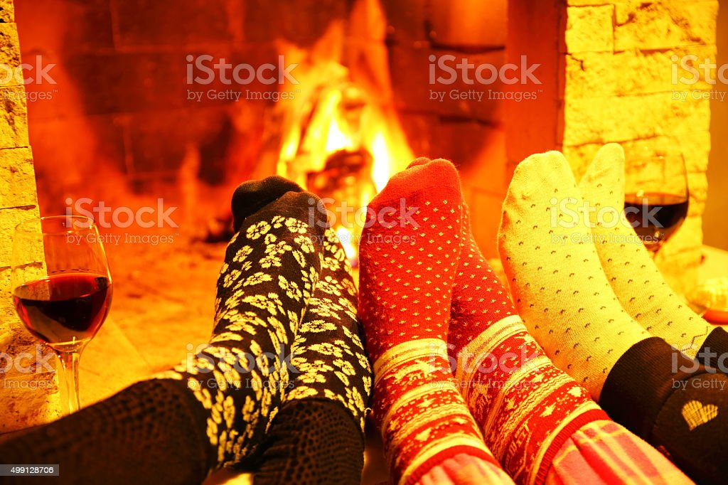 Family wearing woolen socks warming at fireplace stock photo