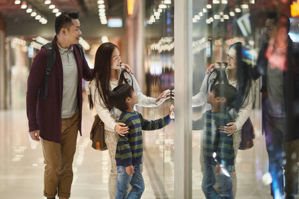 Family window shopping in mall stock photo