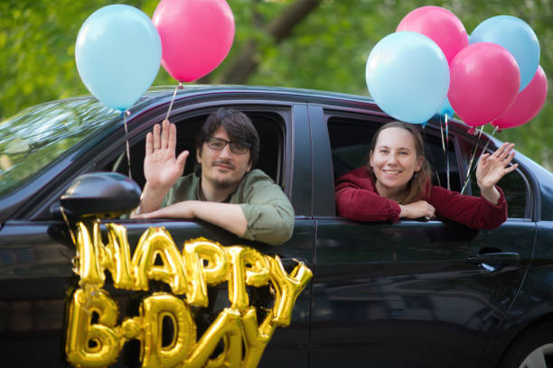 Family wishing Happy Birthday to a friend or relative from their car during an infectious disease epidemic. They are keeping social distancing and wearing protective masks