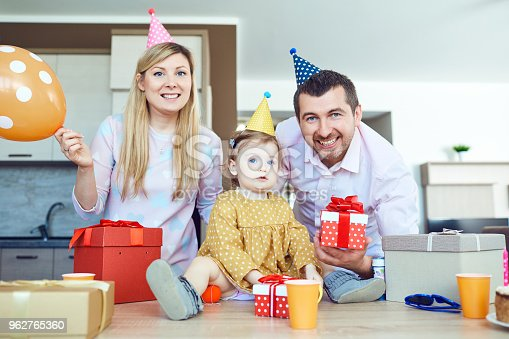 895137896 istock photo A family with a cake congratulates a happy child on his birthday 962765360