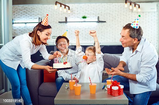895137896 istock photo A family with a candle cake celebrates a birthday party 1003319140