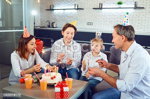 895137896 istock photo A family with a candle cake celebrates a birthday party 1003319172