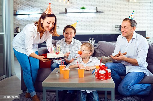 istock A family with a candle cake celebrates a birthday party 941878950