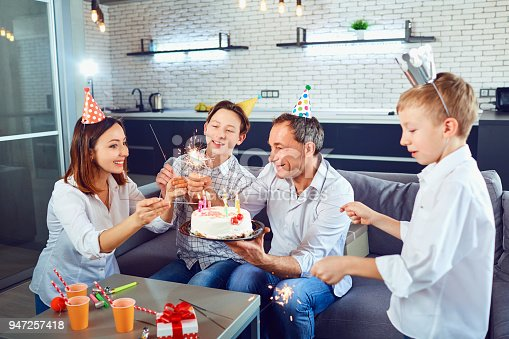 895137896 istock photo A family with a candle cake celebrates a birthday party 947257418