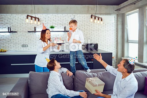 895137896 istock photo A family with a candle cake celebrates a birthday party 947315052