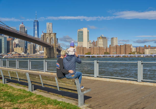 Familie mit einer Tochter mit Blick auf Downtown Manhattan mit der Brooklyn Bridge und dem World Trade Center von DUMBO Brooklyn New York City – Foto