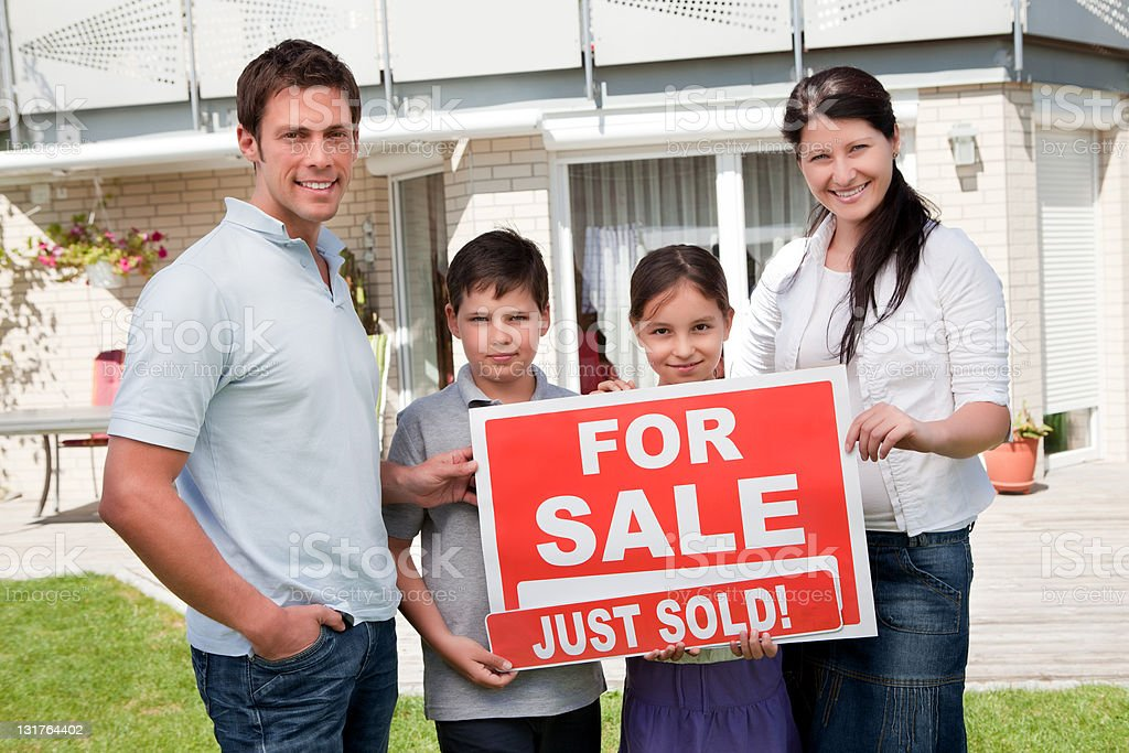 Family with a sale sign outside their new home royalty-free stock photo