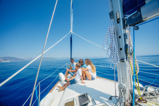 Family with adorable kids resting on yacht stock photo