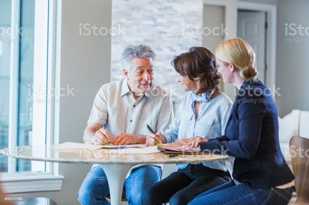 Family with adult daughter working on home finances stock photo