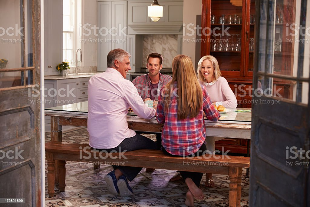 Family With Adult Offspring Enjoying Meal At Home Together stock photo