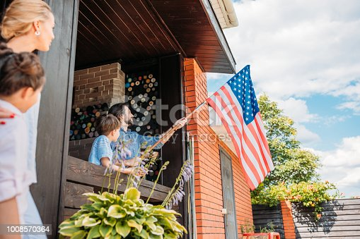 istock family with american flag standing on country house porch 1008570364
