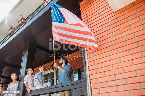 istock family with american flag standing on country house porch 1008570416