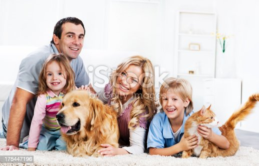 Cheerful parents with their children and pets lying on he carpet at home.