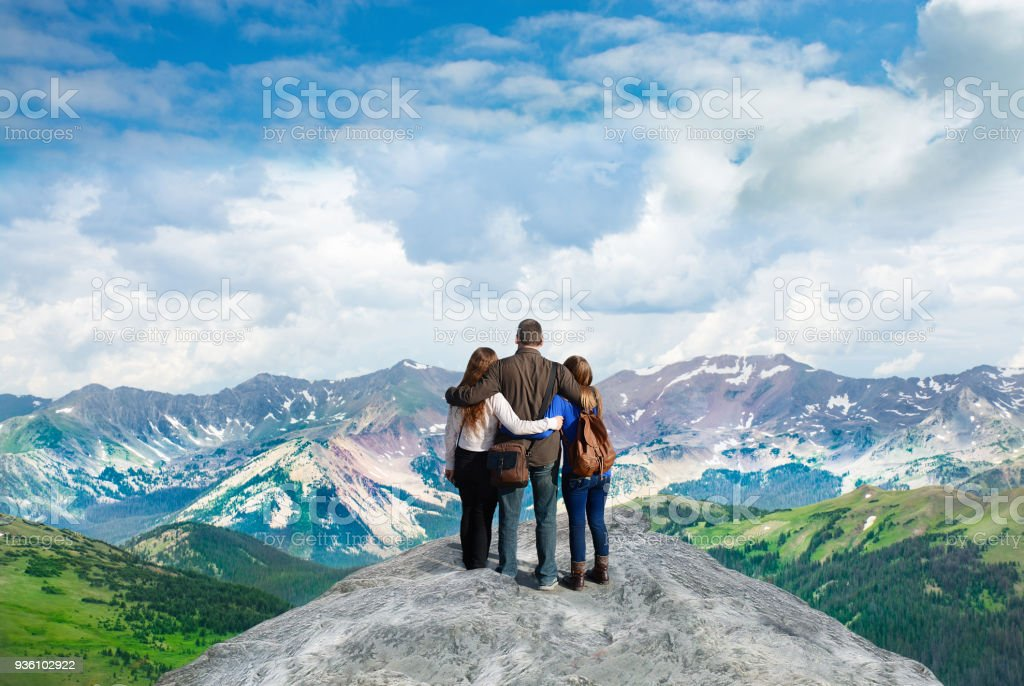 Family with arms around each other enjoying beautiful mountain view on  hiking trip. stock photo