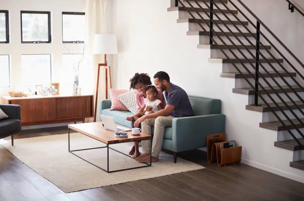 familie mit baby-tochter zu hause auf dem sofa sitzen blick auf laptop-computer - kids tv zimmer stock-fotos und bilder
