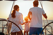 Beautiful happy family enjoying together their vacation on sailboat. They are sitting in cockpit and amazing sunset is in the background