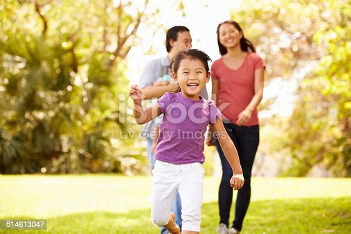 589135214 istock photo Family With Baby In Carrier Walking Through Park 514613047