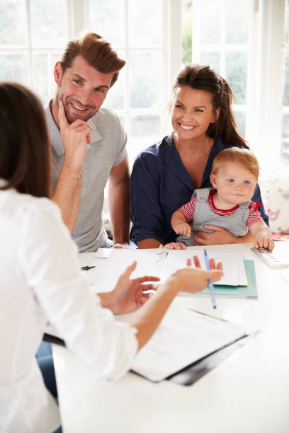 family with baby meeting financial advisor at home - family meeting stock photos and pictures