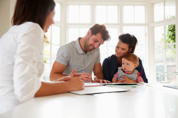 Family With Baby Meeting Financial Advisor At Home Family With Baby Meeting Financial Advisor At Home signing stock pictures, royalty-free photos & images