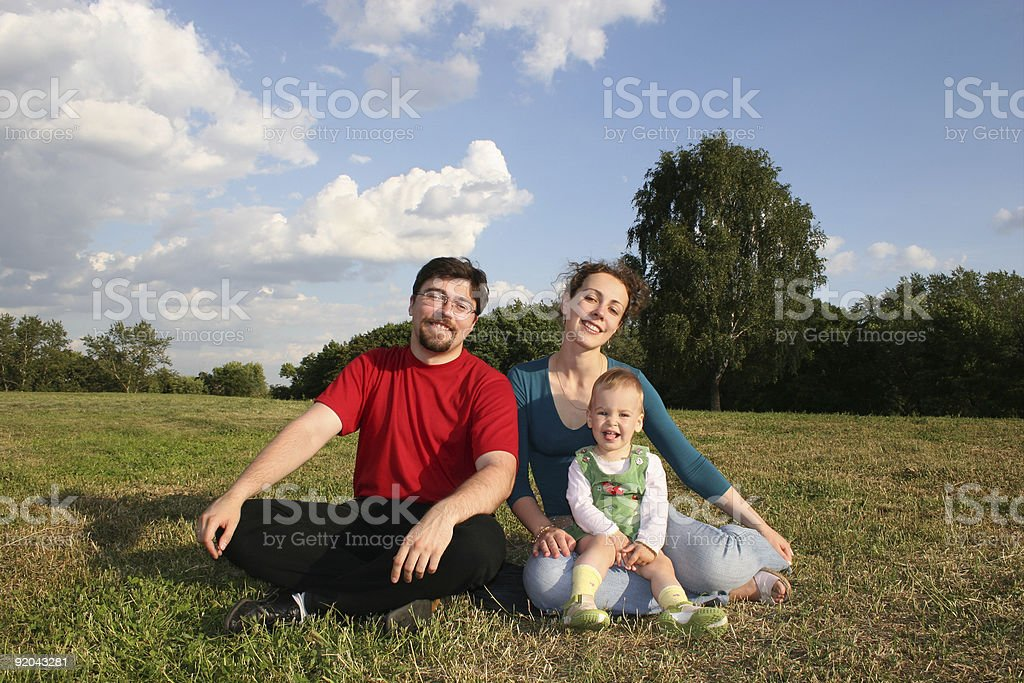 family with baby on meadow and trees 2 royalty-free stock photo