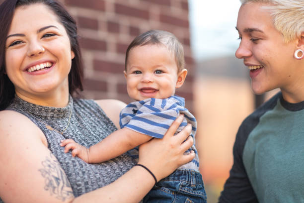 LGBT+ family with baby Portrait of a happy LGBT family. The young adult partners are spending time with their baby outdoors. They are standing near a brick building in a city. The cisgendered parent is holding the baby boy. The parents are smiling at their happy child. cisgender stock pictures, royalty-free photos & images
