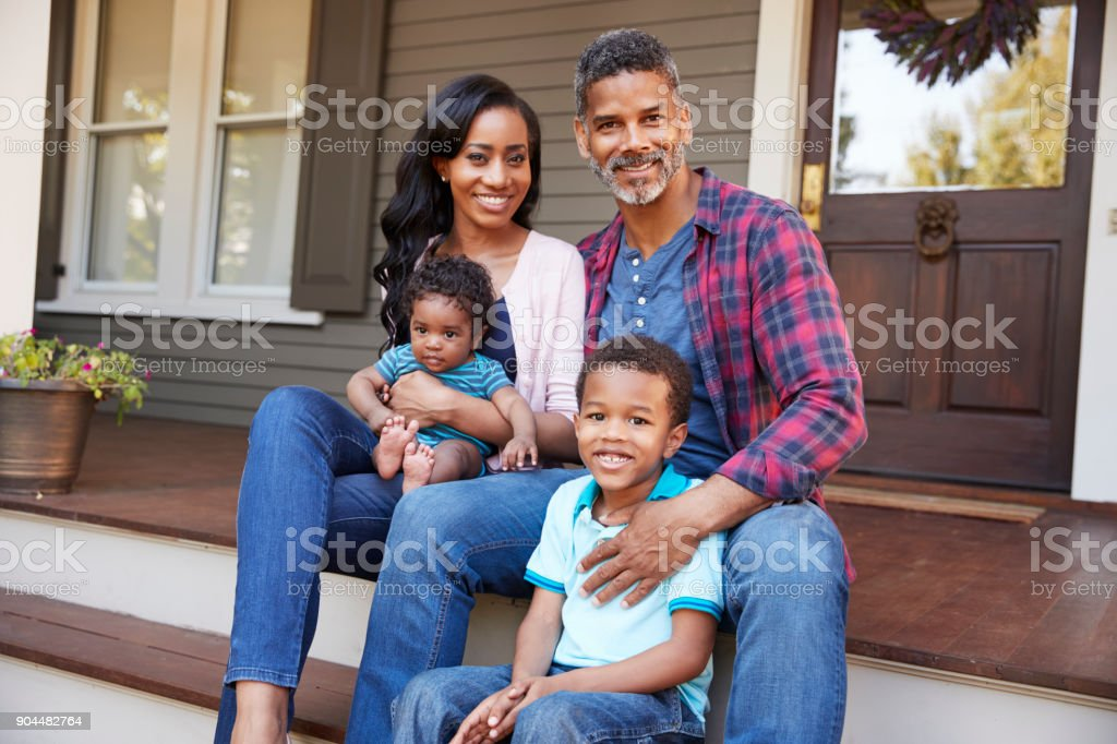 Family With Baby Son Sit On Steps Leading Up To Porch Of Home stock photo