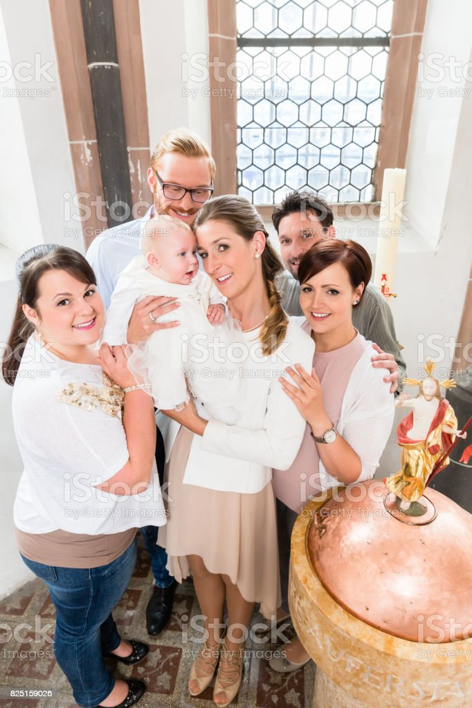 Family with baby standing around the baptismal font stock photo