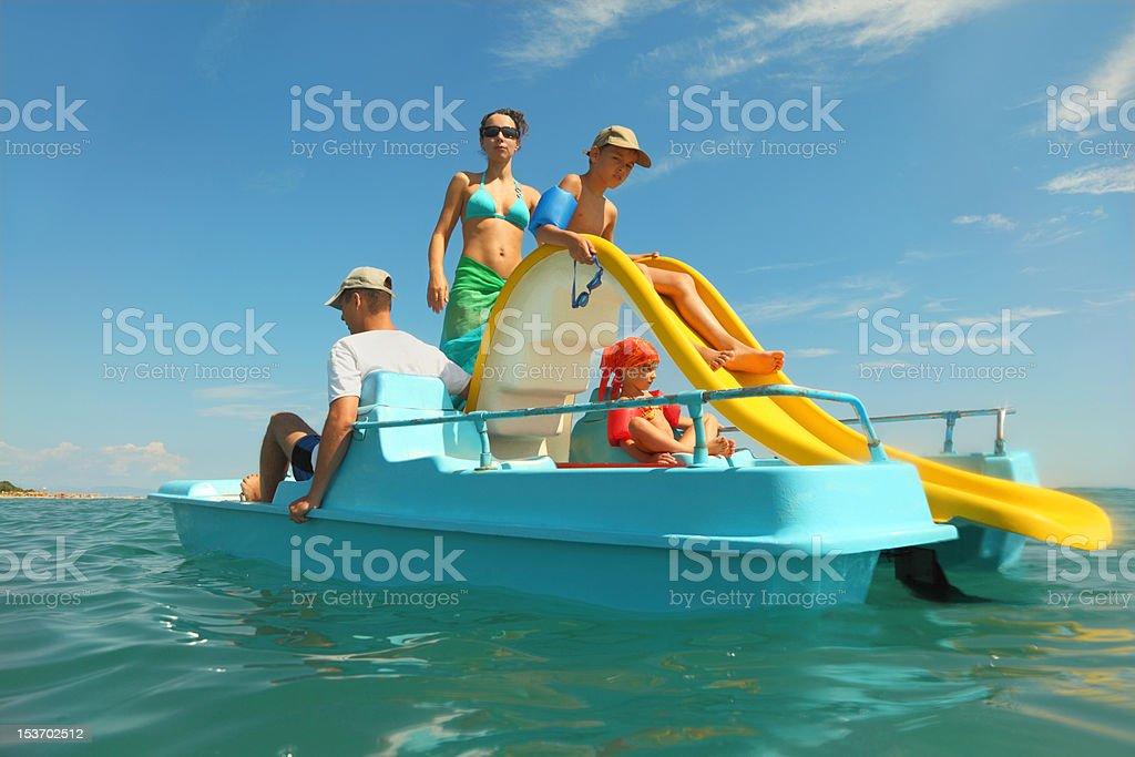 Familia con niño y niña en bote de pedales en el mar - foto de stock