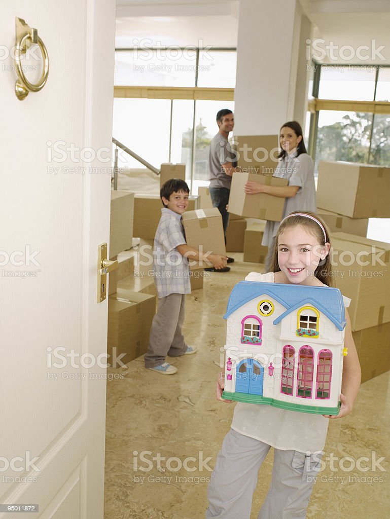 Family with cardboard boxes and dollhouse stock photo