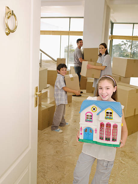 family with cardboard boxes and dollhouse - happy mom packing some toys stock photos and pictures