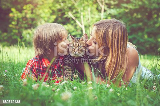 Woman and her son with their cat outdoors in summer