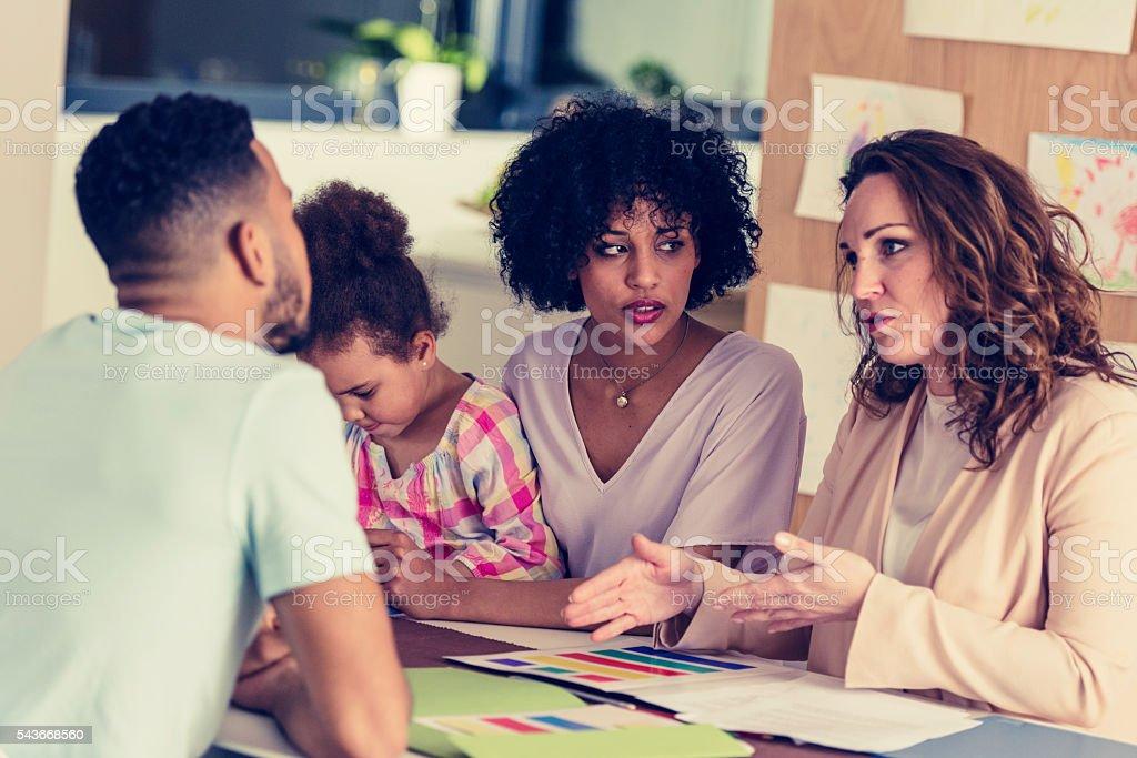 Família com criança falando para as meninas professor - foto de acervo