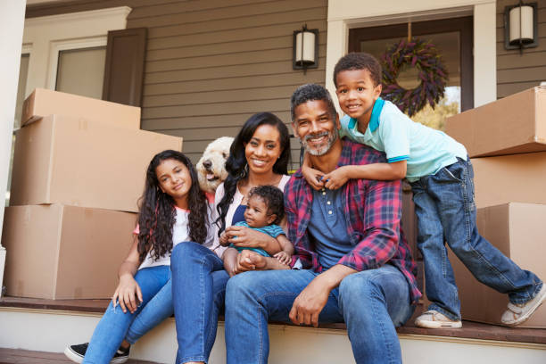 Family With Children And Pet Dog Outside House On Moving Day stock photo