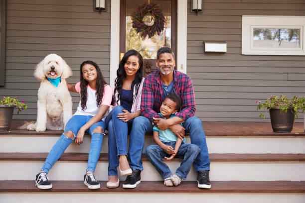 familia con niños y mascota perro sentarse en pasos de casa - africano americano fotografías e imágenes de stock