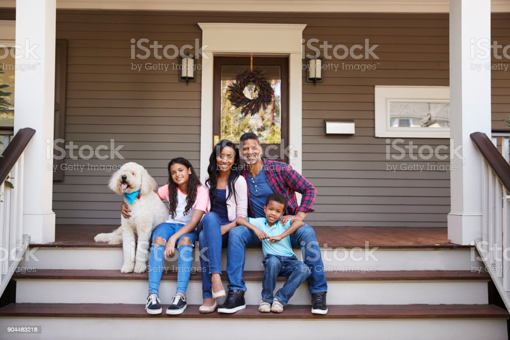 Family With Children And Pet Dog Sit On Steps Of Home stock photo