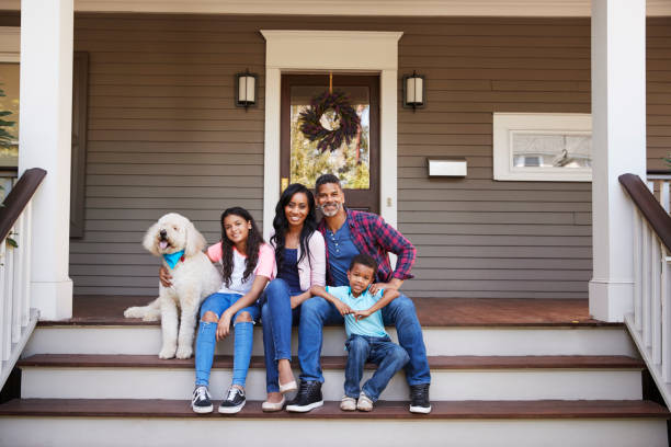 family with children and pet dog sit on steps of home - four people stock photos and pictures