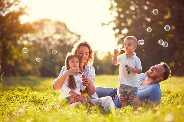Family with children blow soap bubbles stock photo
