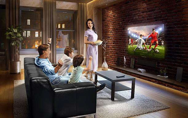 family with children cheering and watching soccer game on tv - fußball themenzimmer stock-fotos und bilder