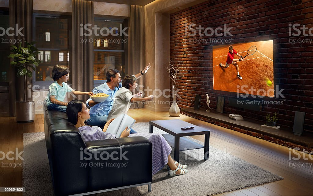 Family with children cheering and watching Tennis game on TV stock photo