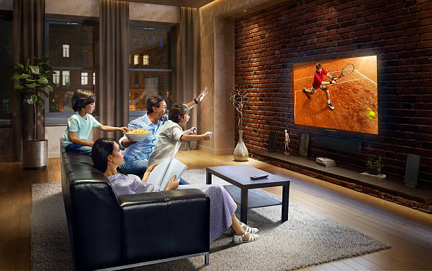 family with children cheering and watching tennis game on tv - family watching tv stock photos and pictures